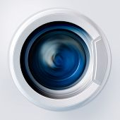 stock photo of washing machine  - Front view and portion of the porthole of the washing machine during washing and rotation of the drum containing clothes blue - JPG
