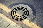 pic of manhole  - Round rusted hatch in urban pavement sewer manhole cover - JPG