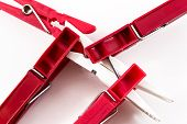 pic of pegging  - Four dark red plastic pegs overcoming a single solitary white plastic peg - JPG