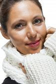 image of snuggle  - Attractive elegant woman in winter fashion snuggling down into her white scarf and black and white jumper to ward off the cold winter weather on white - JPG