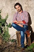 image of wooden crate  - Smiling male model sitting on wooden crate with legs crossed - JPG