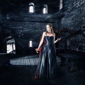 stock photo of aristocrat  - young beautiful female vampire aristocrat with a cup of blood stands in the old castle - JPG