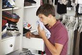 image of wardrobe  - Teenage Boy Checking Freshness Of Clothes In Wardrobe - JPG