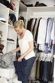 stock photo of wardrobe  - Teenage Girl Choosing Clothes From Wardrobe In Bedroom - JPG