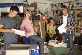 stock photo of yard sale  - Teenage Family Clearing Garage For Yard Sale - JPG