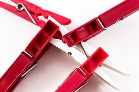 image of pegging  - Four dark red plastic pegs overcoming a single solitary white plastic peg - JPG