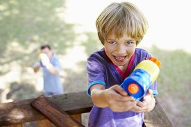 stock photo of pistols  - Father And Son Having Water Pistol Fight In Tree House - JPG