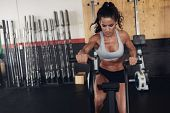 Fit Young Female Working Out On Gym Bike poster
