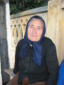 Old Woman Sitting On A Bench