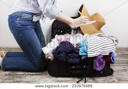 poster of Young Girl Casually Packs Black Suitcase. Packing List In White Notebook