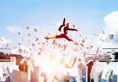 Business Woman Jumping Over Gap With Flying Paper Documents In Concrete Bridge As Symbol Of Overcomi poster