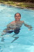 Handsome Smiling Middle Age Man Swimming In Pool