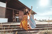 Two boho friends (girls) wearing floral maxi dress and skirt relaxing on the beach. Bohemian clothin poster
