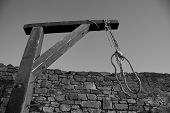 picture of gallows  - gallows with rope preparing for a public execution near a stone wall - JPG