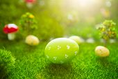 Happy Easter Concept. Colorful Easter Eggs And One Big Green Easter Egg On Spring Green Grass. Fairy poster