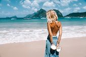 Back view of woman relaxing on the tropical beach, looking at sea landscape and eating coconut. Trav poster