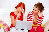 Namoradas desnorteadas olhando na tela de Laptops