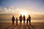Rear View Of Multi Generation Family Silhouetted On Beach poster