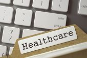 Healthcare Written On  Archive Bookmarks Of Card Index On Background Of White Modern Keypad. Archive poster