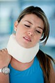 Athletic young woman in pain with a surgical collar