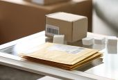 Parcel envelopes ready for shipment to client on table in home office poster