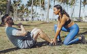 Side view of black sportive girl helping man with abdominal exercise sitting on green meadow in trop poster