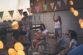 Young Friends Having Fun At A Summertime Rooftop Party, Playing The Guitar, Singing, Dancing And Chi poster