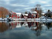 stock photo of marblehead  - Early winter day after snowfall near pond houses reflections in the cold water winter arrived early