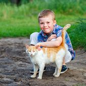 Smiling Little Boy Affectionately Embraces A Red Cat. Outdoor poster