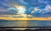 Beautiful sunset with the sun behind colorful clouds over the Aegan sea in Aegina island in Greece - poster