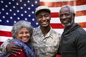 Portrait of a young adult African American male soldier embracing with his parents, all of them smil poster