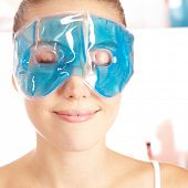 Attractive young woman enjoying cooling eye gel mask in her face