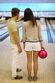 Back of man and woman with pink ball in bowling club; man shows bowling lane; shallow depth of field