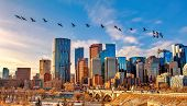 A Flock Of Geese Flying Over Downtown Calgary poster