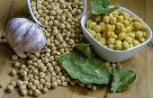 Dried Chickpeas And Boiled Chickpeas Arranged On A Kitchen Counter Top Along With Bay Leaves And Gar poster