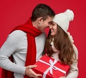 Tender Man Giving Christmas Gift In Red Box And Kissing Charming Woman In White Hat Smiling With Clo poster
