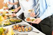 stock photo of buffet lunch  - Catering at business company event people choosing buffet food appetizers - JPG