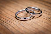 Wedding Rings layingon Natural Wooden Table Or Desk poster