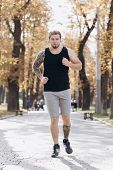Sport Concept. Athlete Workout For Marathon Wearing Earphones And Listening Music. Guy Jogging In Th poster