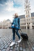 A Young Tourist Girl Arrived In Brussels And Came To The Grand Place With A Suitcase To Look At The  poster