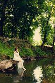 Bride Sitting On Riverbank