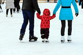 A Little Boy With His Parents Skates On The Ice Rink In The Winter. A Man And Woman Is Teaching Her  poster