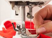 pic of thread-making  - A sewer threading a needle in the sewing machine - JPG