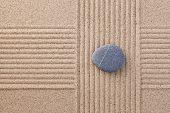 Um único seixo cinzento em um jardim de zen de areia inclinado com criss cruzou seções