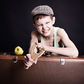 vintage art portrait of liitle boy looking at camera holding catapult and  leaning on old suitcase,