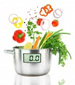 Fresh vegetables falling into a casserole pot with digital weight scale