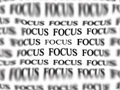 The word focus with blurred words in background isolated on white as concept for business ideas