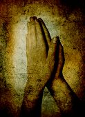 Hands of a person raised together in prayer sepia toned