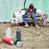 Spray paint cans on the sand in front of a large spray painted graffiti wall, with an artist, posing