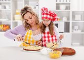 Mother and little girl making a cake together - spreading the filling